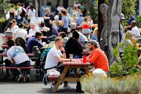 Ihmiset istuivat oluella Thames-joen rannassa Lontoossa perjantaina.