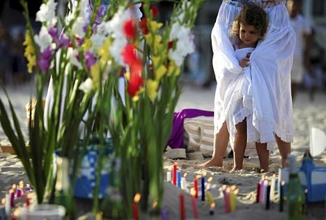 Pikkutyttö piteli kiinni äitinsä hameesta Copacabanalla, jossa afrobrasilialaisen umbanda-uskonnon perinteen mukaan tarjotaan vuoden vaihteessa kukkia meren äidille Yemanjálle.