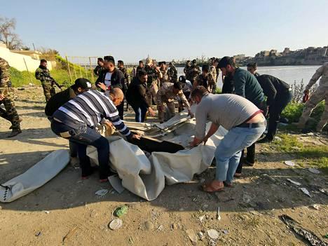 Irakilaiset avustivat lauttaonnettomuuden jälkeen torstaina Tigrisjoella.