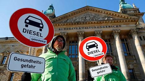 """Greenpeacen mielenosoittajat odottelivat tiistaina korkeimman hallinto-oikeuden edessä oikeuden päätöstä Leipzigissä. Julisteessa kerrotaan, että diesel on """"terveysvaara""""."""