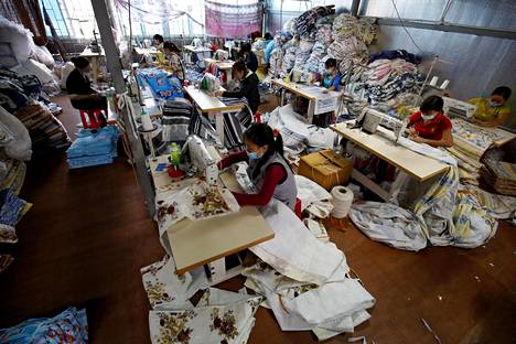 Työntekijät työskentelivät tekstiilitehtaalla Hanoin esikaupunkialueella Vietnamissa maaliskuussa.