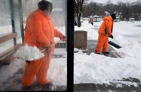 Kaupungin työntekijät lapioivat lunta pois bussipysäkeiltä Washingtonissa perjantaina.