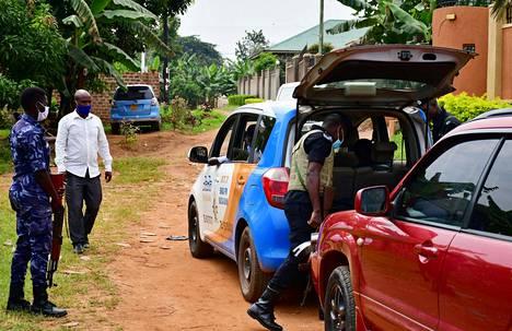 Ugandalaiset turvallisuusviranomaiset tutkivat ajoneuvoja oppositiojohtaja Bobi Winen kodin edustalla Kampalan Mageressa perjantaina.