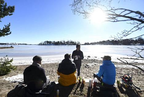 Ulkoilijat nauttivat auringosta piknikillä Mustikkamaalla Helsingissä helmikuun lopulla.