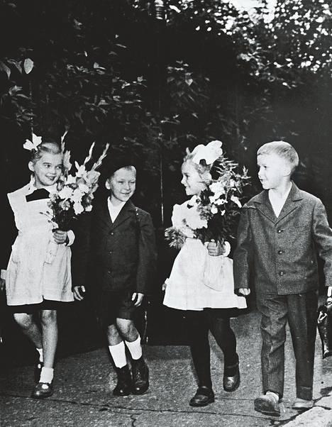 Neuvostoliiton opetusministeriön hyväksymää uutta koulu-univormua esittelevät nämä pirteät neuvostolapset Moskovassa. Tyttöjen asut ovat pysyneet samanlaisina, kun taas poikien ovat perinpohjin muuttuneet. Aikaisempi univormu muistutti lähinnä sotilaspukua.