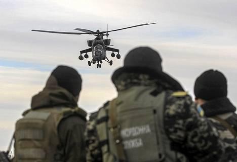 Ukrainalaiset sotilaat seurasivat partioivaa Venäjän armeijan MI-35-helikopteria tarkastuspisteellä Strelkovossa Krimin rajalla Ukrainassa maaliskuussa.