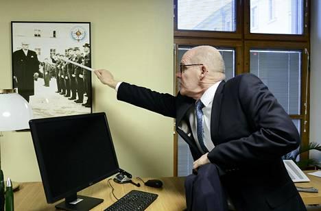 Jukka Juusti osoittaa työhuoneessaan olevasta kuvasta isäänsä Matti Juustia. Kuvassa presidentti Urho Kekkonen tarkastaa ensimmäistä Suezille lähtevien rauhanturvaajien joukkoa vuonna 1956.