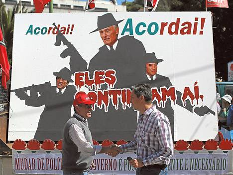 Portugalilaiset vastustivat leikkauksia vappuna Lissabonissa. Kyltissä maan pääministeri, presidentti ja varapääministeri kuvattiin gangstereiksi.