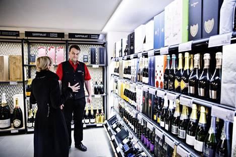 Päivi Meuronen osti perjantaina  keskustan Alkosta taiteilijaystävilleen lahjaksi luomusamppanjaa taide näyttelyn avajaisten kunniaksi. Myyjä Jouko Nieminen opasti valinnassa.