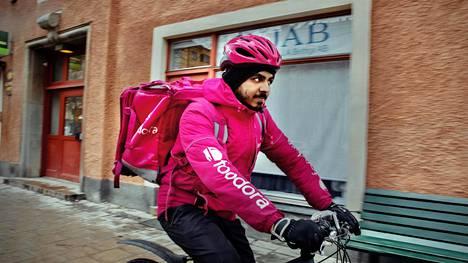 Tukholman Södermalmilla sähköpyörällään ruokaa toimittanut Waleed Banaras kertoo viihtyvänsä ruokakuriirin työssä.