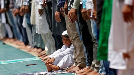 Muslimipoika istui rukoushetkeen saapuneiden muslimimiesten joukossa Mumbaissa ramadanin paastokuukauden viimeisenä perjantaina kesäkuussa 2017.