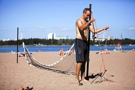 Timo Koskiniemi pystyttää beach-tennisverkkoa Hietarannan uimarannalla. Hän on tutustunut beach-tennikseen tänä kesänä. Aiemmin kesällä Hietsussa ei ole näkynyt juuri auringonottajia, mutta nyt helleaallon aikaan tilanne on toinen.