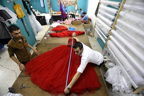 Palestiinalainen al-Ashi-perheen suunnittelija mittasi iltapukua ateljeessa Gaza Cityssä.
