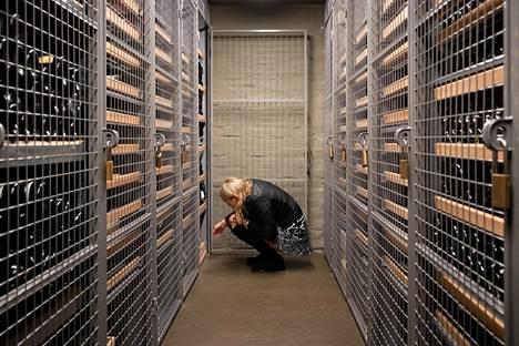 Sanni Sojonen etsii tuliaisviiniä kaapistaan viinikellarissa.