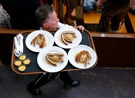 Tarjoilija kantoi makkaraa asiakkaille Oktoberfestissä Münchenissä. Ylipaino on yksi eurooppalaisten isoimmista terveysriskeistä.