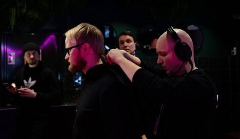 Äänitarkkailija Jousia Lappi asettaa Vahvaselle mikrofonin.