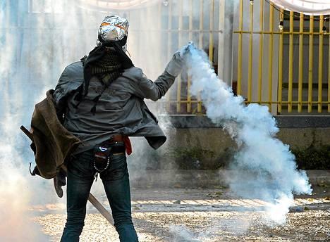 Hallitusta vastustava mielenosoittaja heitti takaisin poliisin kyynelkaasupommin Bangkokissa torstaina.