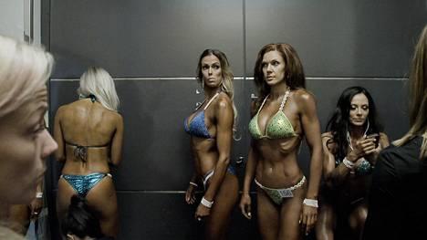 Bikini fitness -kilpailijat jonottavat lavalle Muodonmuutos-dokumentissa.