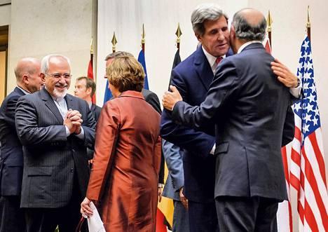 Iranin ulkoministeri Javad Zarif (toinen vas.) puhui EU:n ulkosuhdejohtaja Catherine Ashtonille (selin), ja Yhdysvaltain ulkoministeri John Kerry (toinen oik.) halasi Ranskan ulkoministeriä Laurent Fabiusta Genevessä sunnuntaina sopimuksen syntymisen jälkeen.