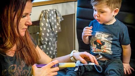 Konstantin lounaalla. Hänen äitinsä Elina Kela ruiskuttaa ravitsemusliuoksen letkuun, jota pitkin se valuu suoraan vatsaan.