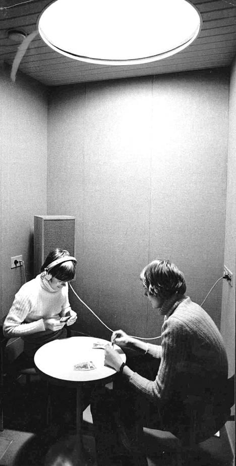 Töölön kirjastotalon musiikkikabinetteihin mahtuu kaksi henkilöä kerrallaan. Stereorytmejä kuuntelevat korttipelin lomassa veljekset Matti ja Antti Hietanen.