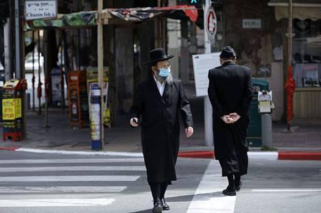 Kasvosuojaan pukeutunut Bnei Barkin asukas ylitti kaupungin katua maanantaina.