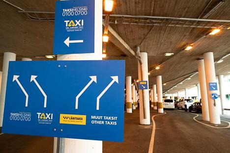 Kyltit ohjaavat taksit omiin jonoihinsa Helsinki-Vantaan lentoaseman taksitolpalla.