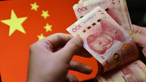August 20, 2020, Fuyang, China: In this photo illustration a man counts 100 RMB notes with the Chinese flag in the background..In recent years, China has clamped down on shadow banking,concerned about the hidden risks in the high volume of complexand potentially risky loans in the sector. As a weakeningeconomy puts pressure on businesses and individuals, authoritiesfear shadow lending and illegal loans might surge. (Credit Image: © SheldonCooper/SOPA Images via ZUMA Wire)