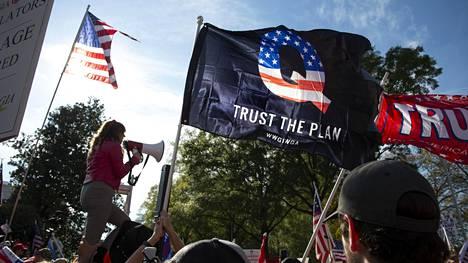 Qanon-salaliittoteorian tunnuslippu liehui Donald Trumpin kannattajien tilaisuudessa Georgian pääkaupungissa Atlantassa marraskuussa.