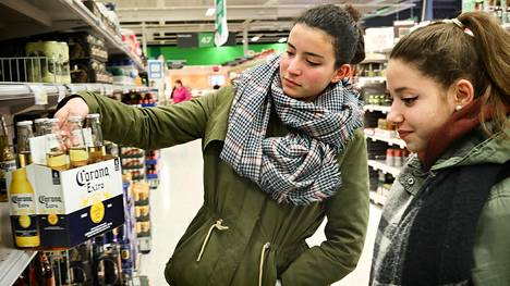 """Maria Romero (vas) ja Veronica Quintanilla vertailivat oluen hintoja Sellon Prismassa Espoon Leppävaarassa. Espanjalaisten näkökulmasta Suomen alkoholipolitiikka vaikuttaa tiukalta. """"Väkeviä oluita, viinejä ja tällaisia voisi mielestäni myydä ruokakaupassa. Viinat voisivat jäädä erilleen"""", Quintanilla sanoo."""