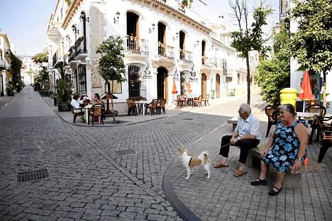 Pariskunta istuu koiran kansa kadunkulmassa Marbellan vanhassa kaupungissa.
