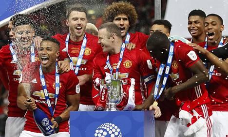 Manchester Unitedin Wayne Rooney vahtii voittopokaalia.