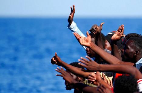 Kumiveneellä Välimerellä matkustaneet siirtolaiset heiluttivat pelastusalusta apuun Libyan rannikolla syyskuussa.