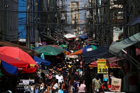 Ihmisiä kulkemassa ruuhkaisella ostoskadulla Luoteis-Brasiliassa sijaitsevassa Manausin kaupungissa lauantaina.