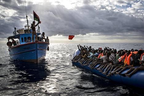 Libyalaiset kalastajat heittivät pelastusliivit kumiveneeseen täynnä siirtolaisia. Viime vuonna otettu kuva ei liity maanantain tragediaan.