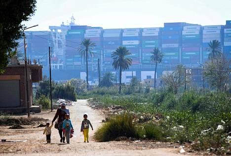 Nainen kävelee lasten kanssa Koillis-Egyptin Ismailiya-kaupungissa. Edessä MV Ever Given (Evergreen) konttialus, jonka karilleajo estää laivaliikenteen Suezin kanaalilla.