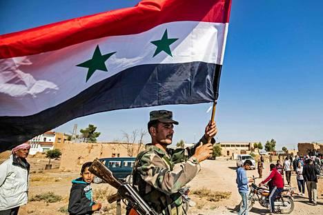 Syyrian asevoimien sotilas heiluttaa Syyrian lippua joukkojen saavuttua Koillis-Syyriaan Tal Tamrin kylään maanantaina.