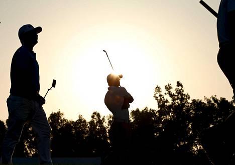 Euroopan ykköspelaaja Rory McIlroy (keskellä) ja muut kärkimiehet ehtivät pelata ennen auringonlaskua puolet kolmannesta kierroksesta.