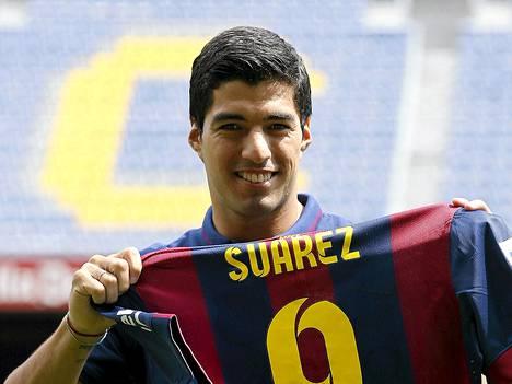 Luis Suarez hymyili uuden joukkueensa paidan kanssa kuvaajille.