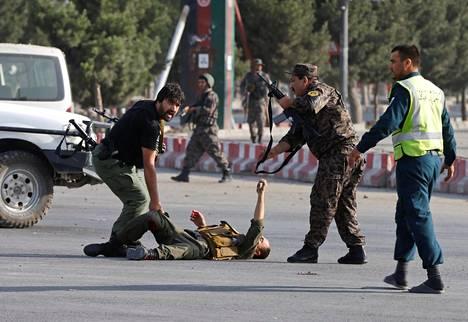 Kabulin sunnuntaisessa räjähdyksessä loukkaantunutta miestä autettiin ylös kadulta.