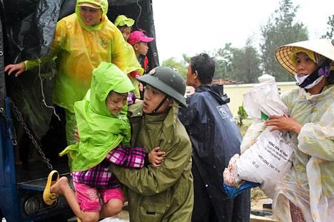 Sotilas avusti evakuoitavia kyläläisiä ulos autosta Quang Namin provinssissa Vietnamissa lauantaina.