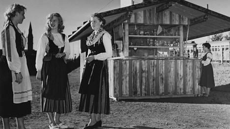 Kansallispukuiset suomalaisnaiset myivät Kalevala-koruja kojusta vuonna 1952.