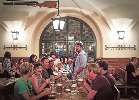 Seurue laulaa ja nautiskelee müncheniläisessä olutkellarissa.