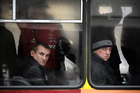 Bussimatkustajia Donetskin keskustassa Ukrainassa torstaina. Tykistötuli jatkui lähellä kaupungin tuhoutunutta lentokenttää.