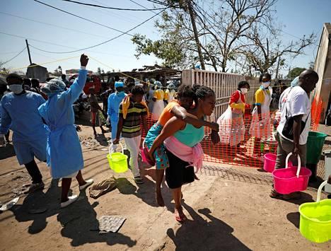 Nainen kantoi naista selässään terveysaseman ulkopuolella Beirassa Mosambikissa tiistaina.
