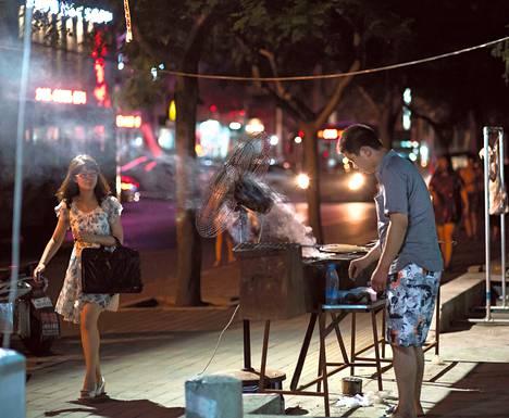 Nainen käveli katugrillin ohi heinäkuussa 2013, jolloin Peking oli jo kieltänyt katugrillit.