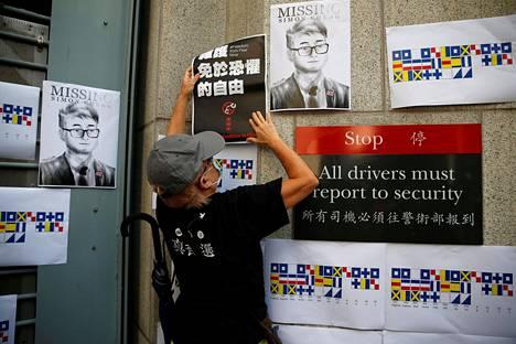 Mielenosoittaja kiinnitti julistetta Simon Chengin kuvien viereen Britannian konsulaatin seinään Hongkongissa keskiviikkona.