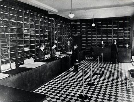 Pullohyllyt ulottuivat lattiasta kattoon Alkon myymälässä pian kieltolain kumoamisen jälkeen 1930-luvulla. Myymälän sijainnista ei ole tietoa.