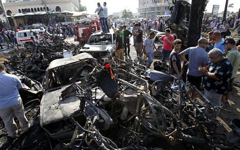 Tripolilaisia kerääntyi perjantaina al-Taqwan moskeijan luo tutkimaan pommi-iskun jälkiä.