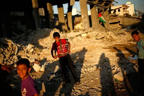 Palestiinalaispojat leikkivät tuhoutuneen talon raunioissa Gazassa torstaina.